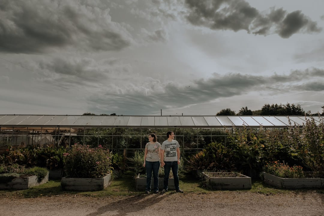 couple standing at secret herb garden with moody sky