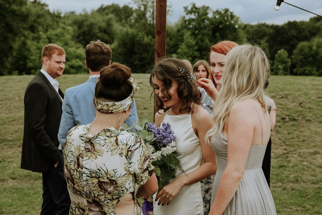 brides-friends-gather-round-flower-crown-artistic-wedding-photography-leicestershire