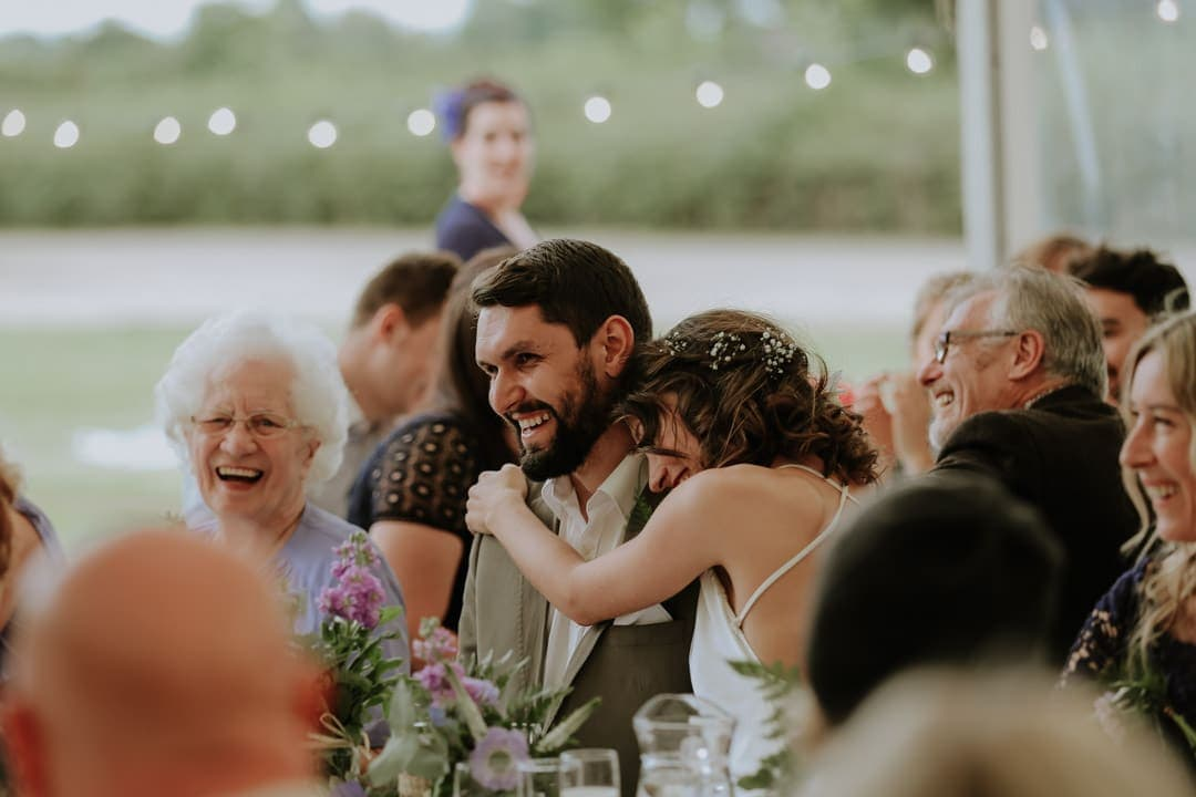 bride-hugs-laughing-groom-diy-marquee-wedding-leicestershire-wedding-photographer