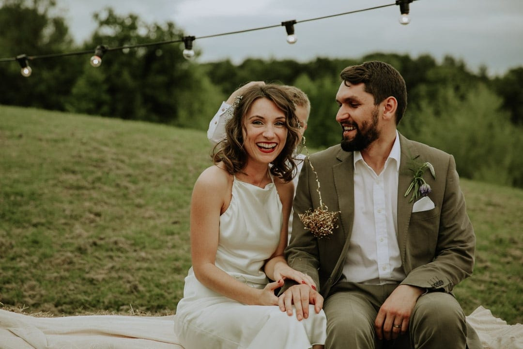 cool-bride-groom-sitting-haybales-diy-leicestershire-wedding