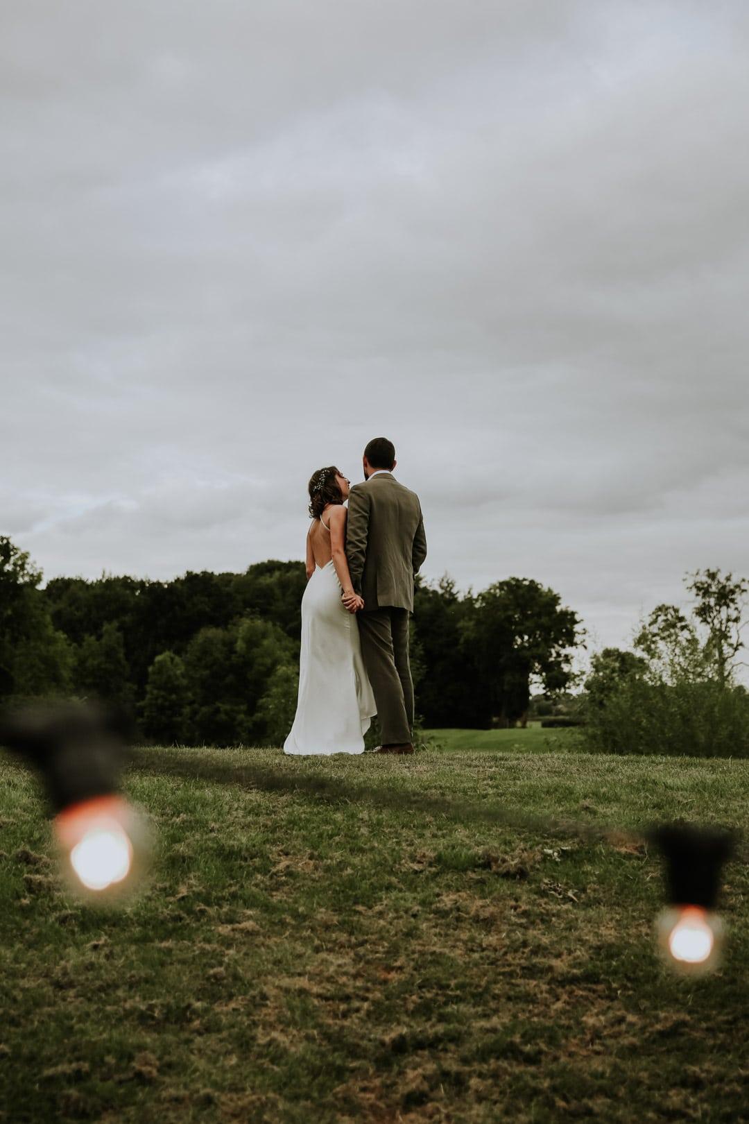 bride-groom-hold-hands-backless-satin-wedding-dress
