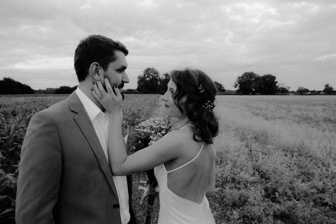 bride-holds-grooms-cheek-showing-wedding-ring-field