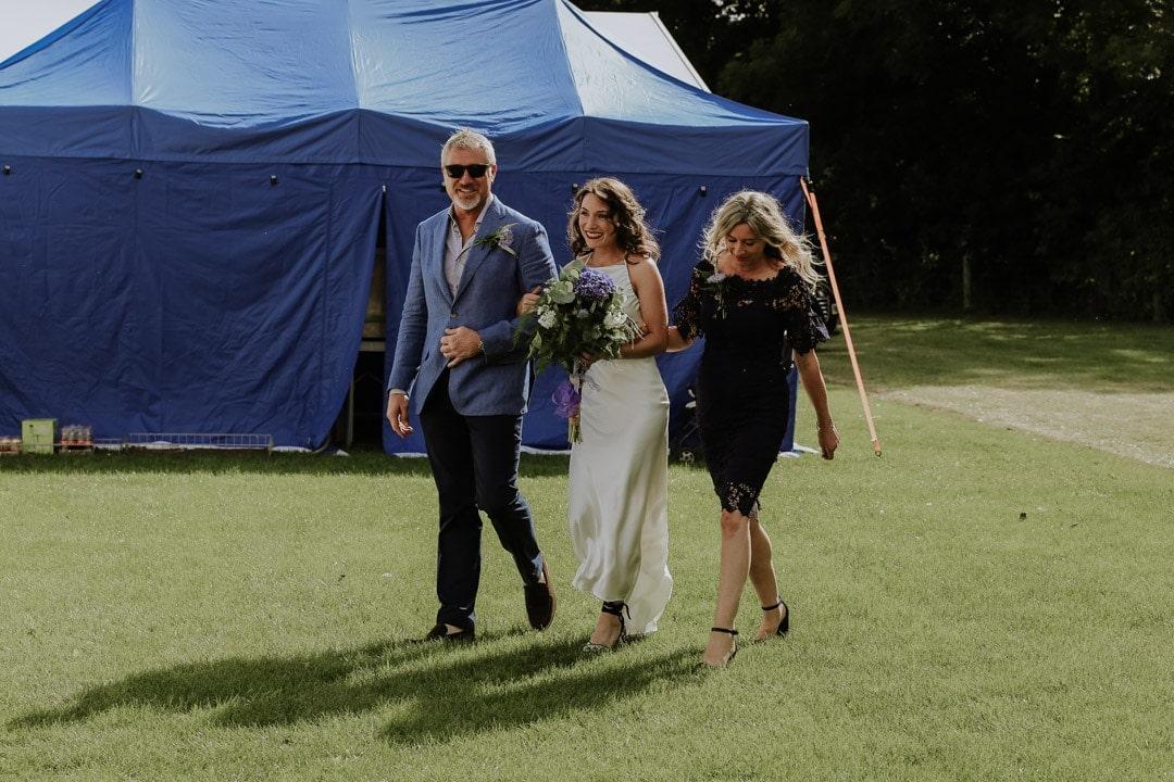bride-wearing-satin-dress-walks-toward-groom-with-parents