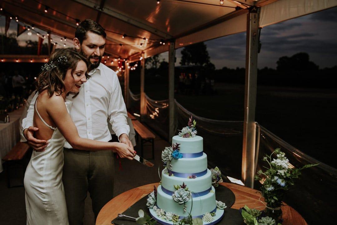 bride-groom-cut-cake-marquee-wedding-leicestershire