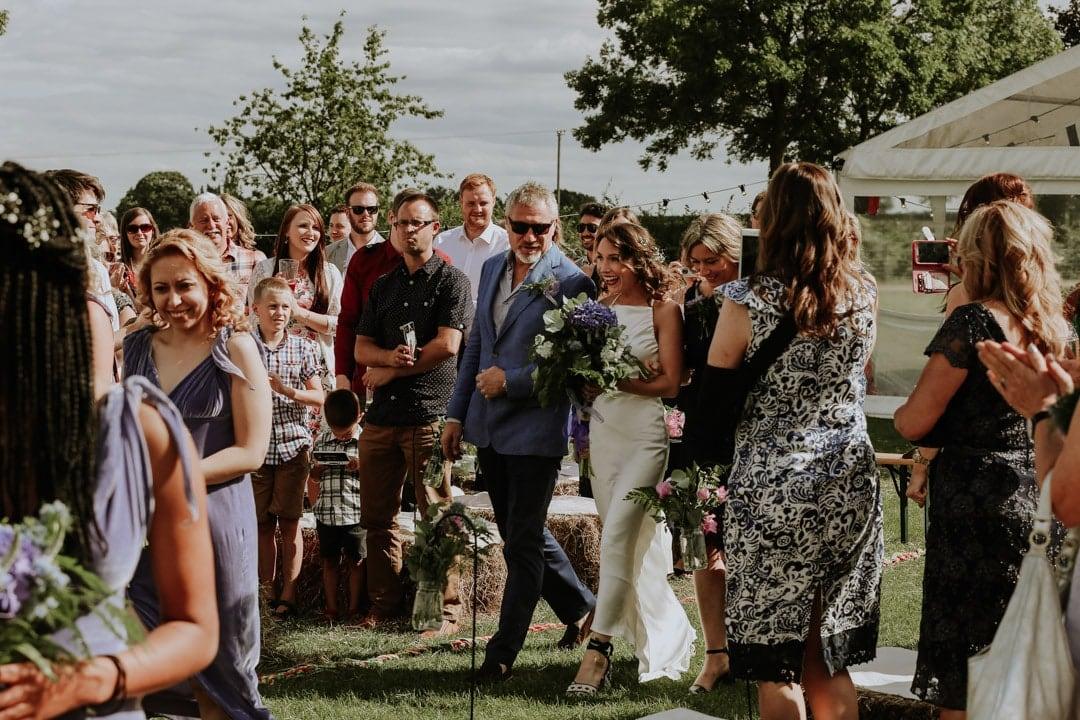 bride-walking-towards-groom-wildflower-bouquet-diy-farm-wedding