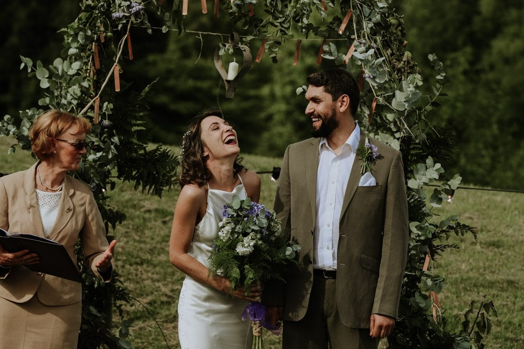 bride-lauging-during-ceremony-large-wildflower-bouquet
