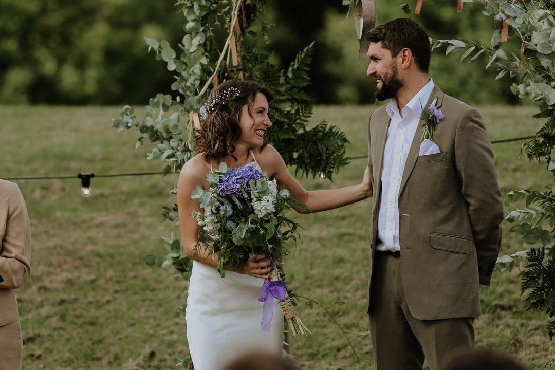 bride-wearing-flower-crown-greets-groom-under-flower-arch
