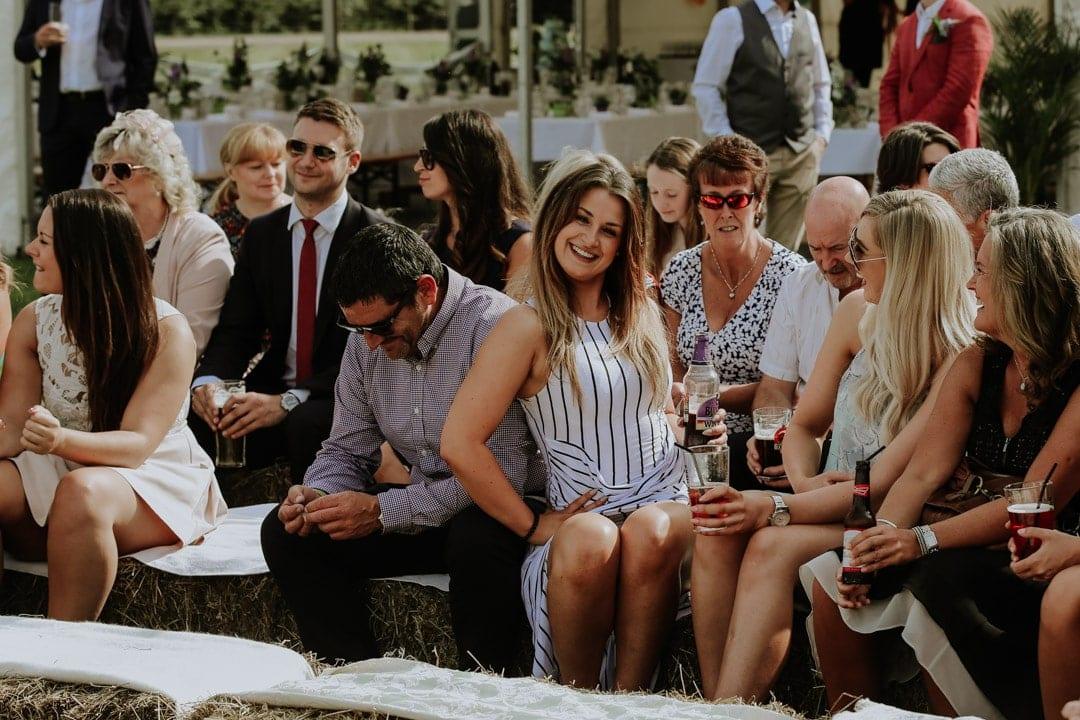 stylish-wedding-guests-sitting-hay-bale-seating-farm-wedding