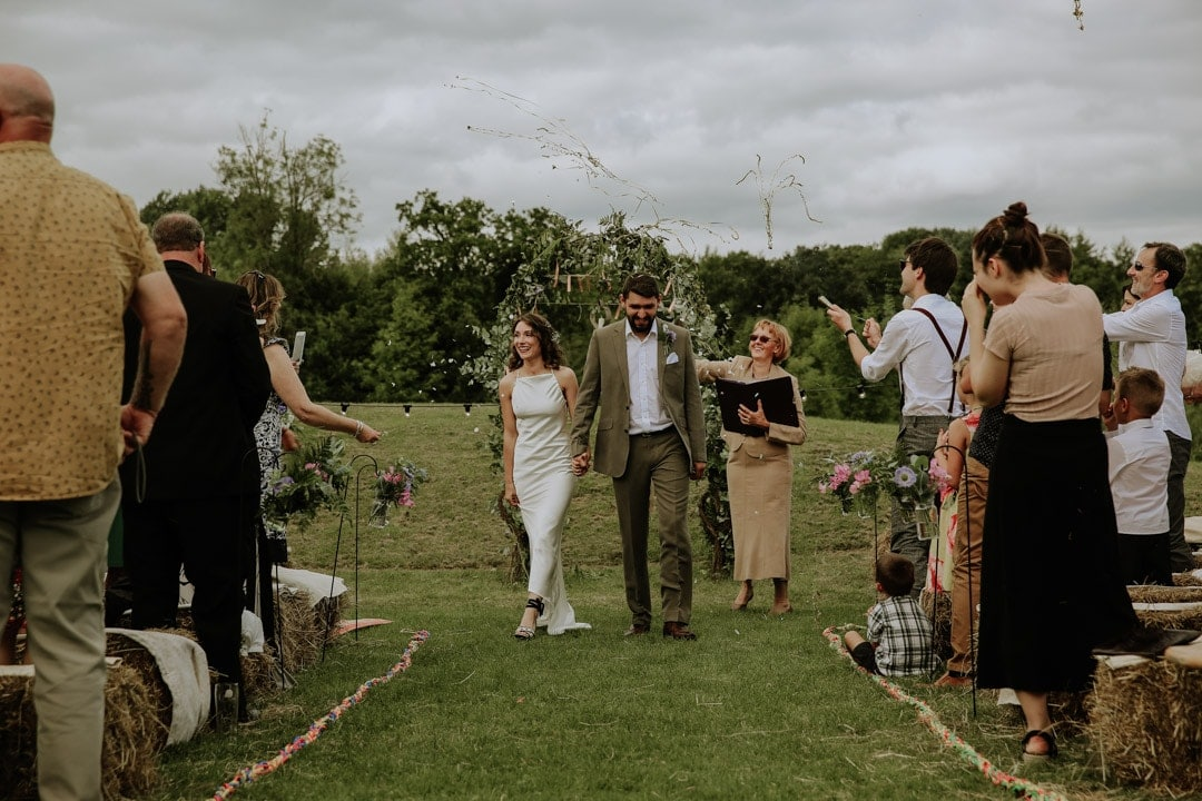 golden-streamers-confetti-bride-walks-down-aisle-with-groom-diy-leicestershire-wedding