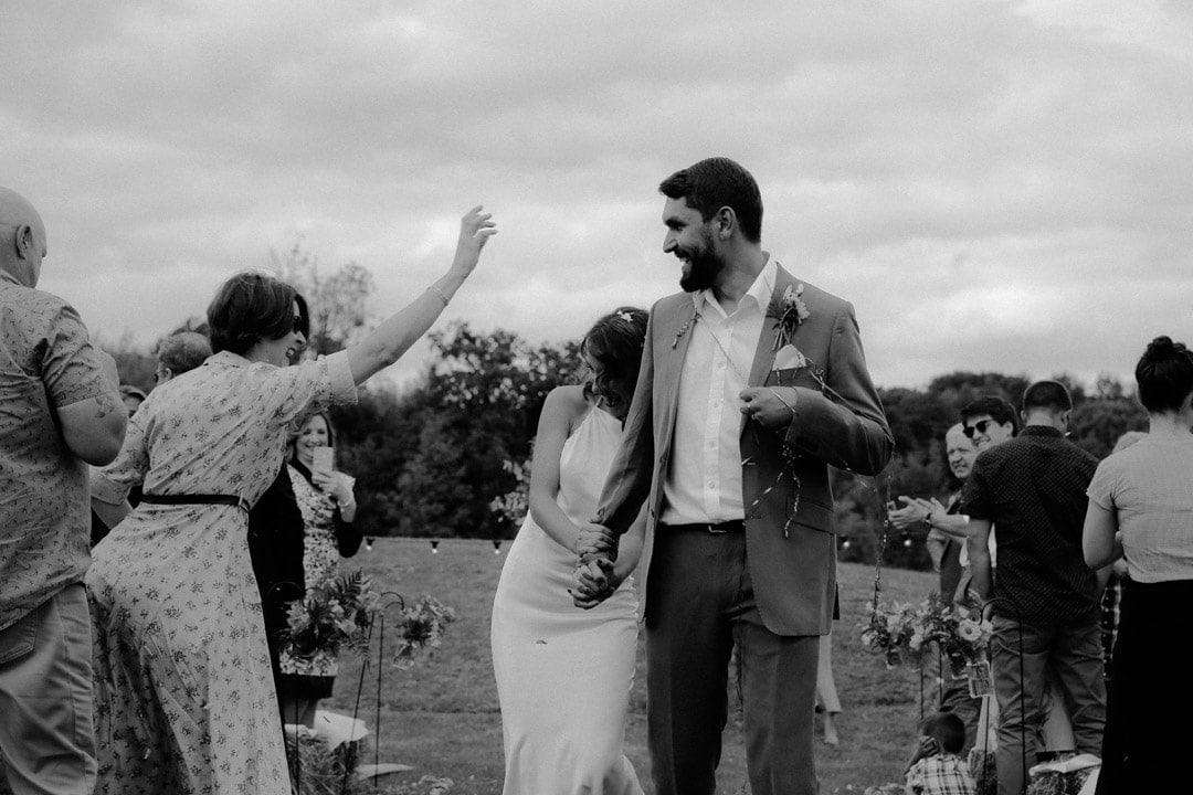 bride-wearing-long-satin-dress-laughs-with-groom-diy-farm-wedding
