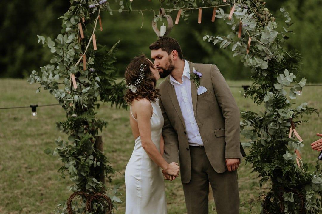 groom-kisses-bride-during-outdoor-wedding-ceremony-christine-mcnally-wedding-photography