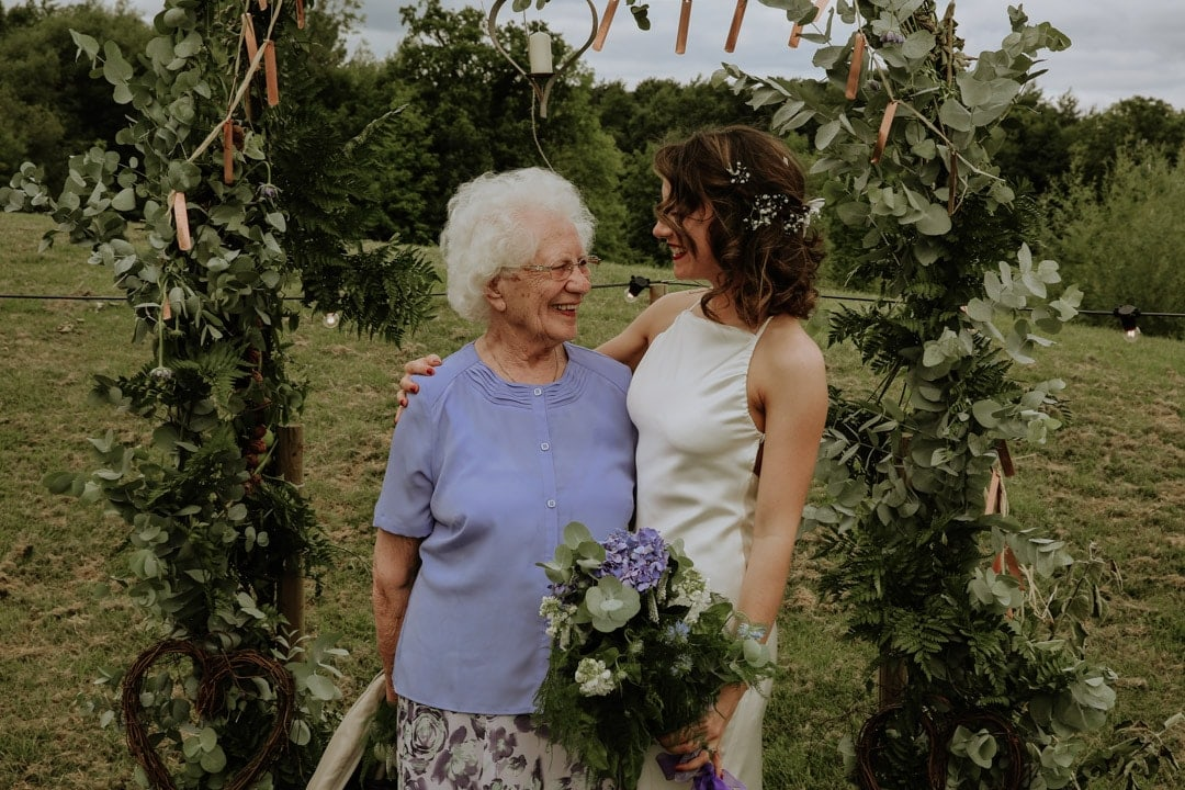 formal-group-shot-bride-with-grandma-under-flower-arch