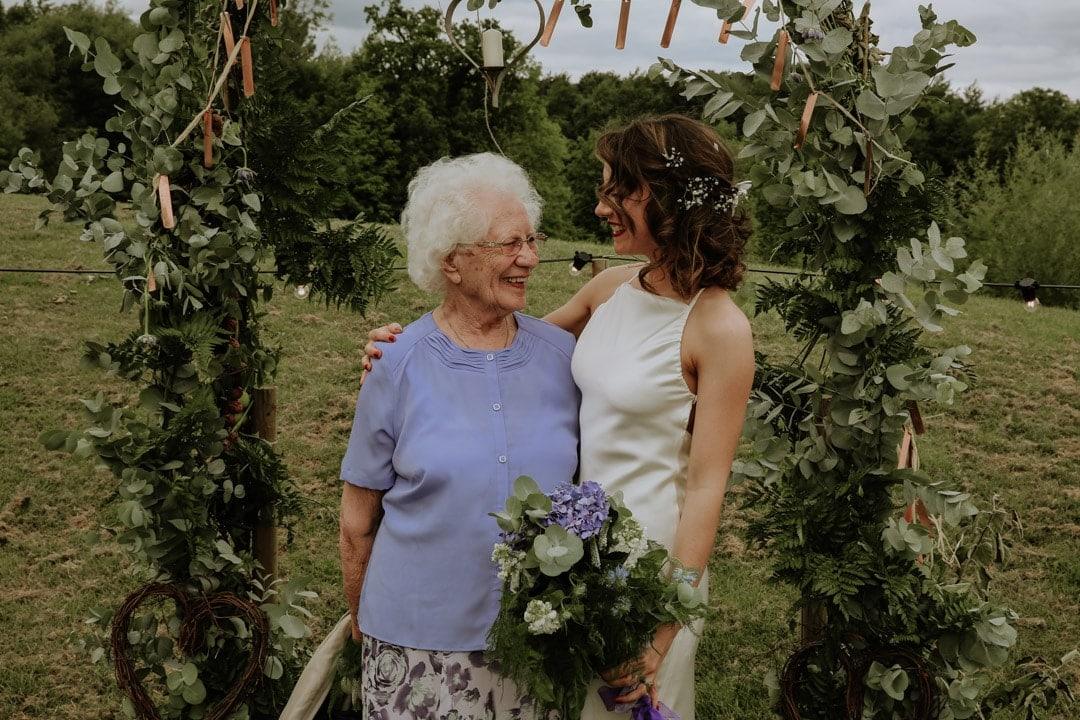 formal-group-shot-bride-with-grandma-under-flower-arch