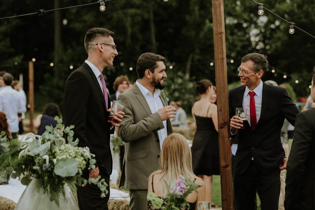 groom-wearing-relazed-green-suit-talks-with-guests-leicestershire-diy-wedding