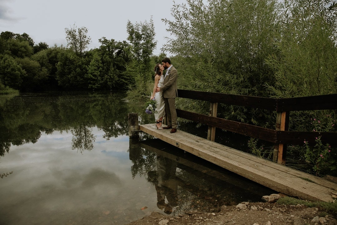 bride-kisses-groom-reflected-lake-outdoors-wedding-leicestershire
