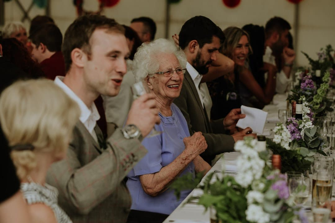 brides-laughing-grandma-seated-tressel-table