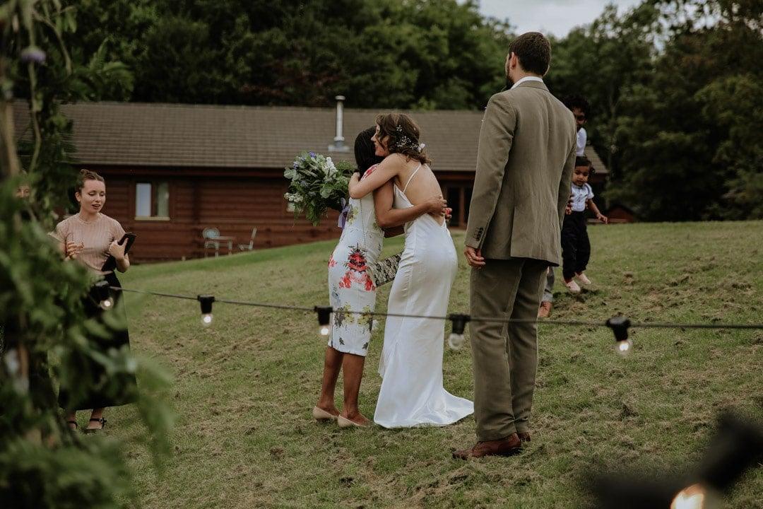 bride-hugs-guest-holding-large-wildflower-bouquet